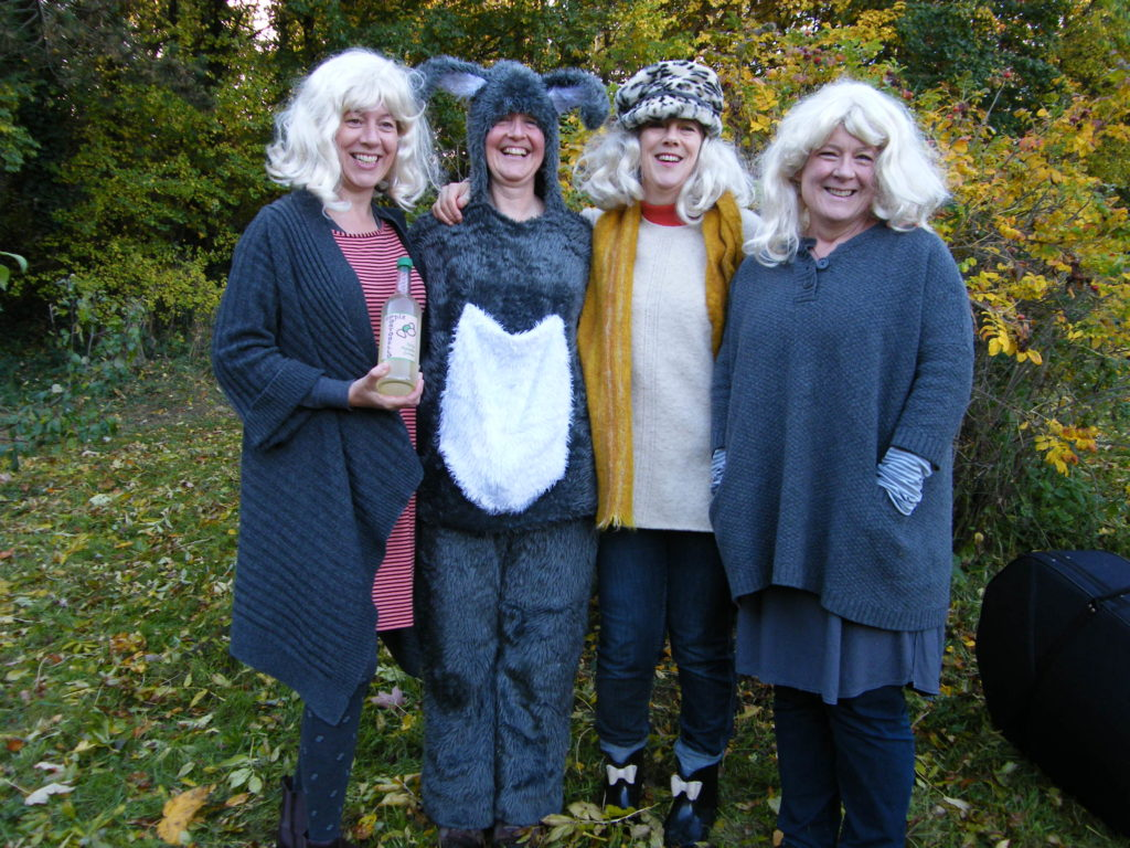 Four women standing in the orchard - 3 wearing blond ewigs, one wearing a rabbit suit