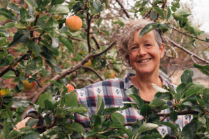 Jane looking through the branches of an apple tree
