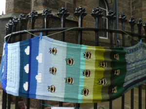 Knitted bees on a blue and green background, tied to railings