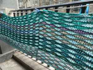 Knitted pane with stitches to give the effect of waves hanging on raillings